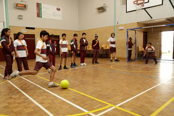 A group of students playing indoor soccer in the school hall.