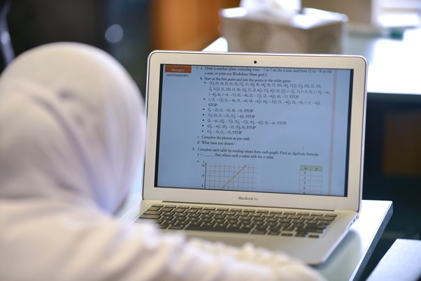 Student using online maths textbook on her laptop