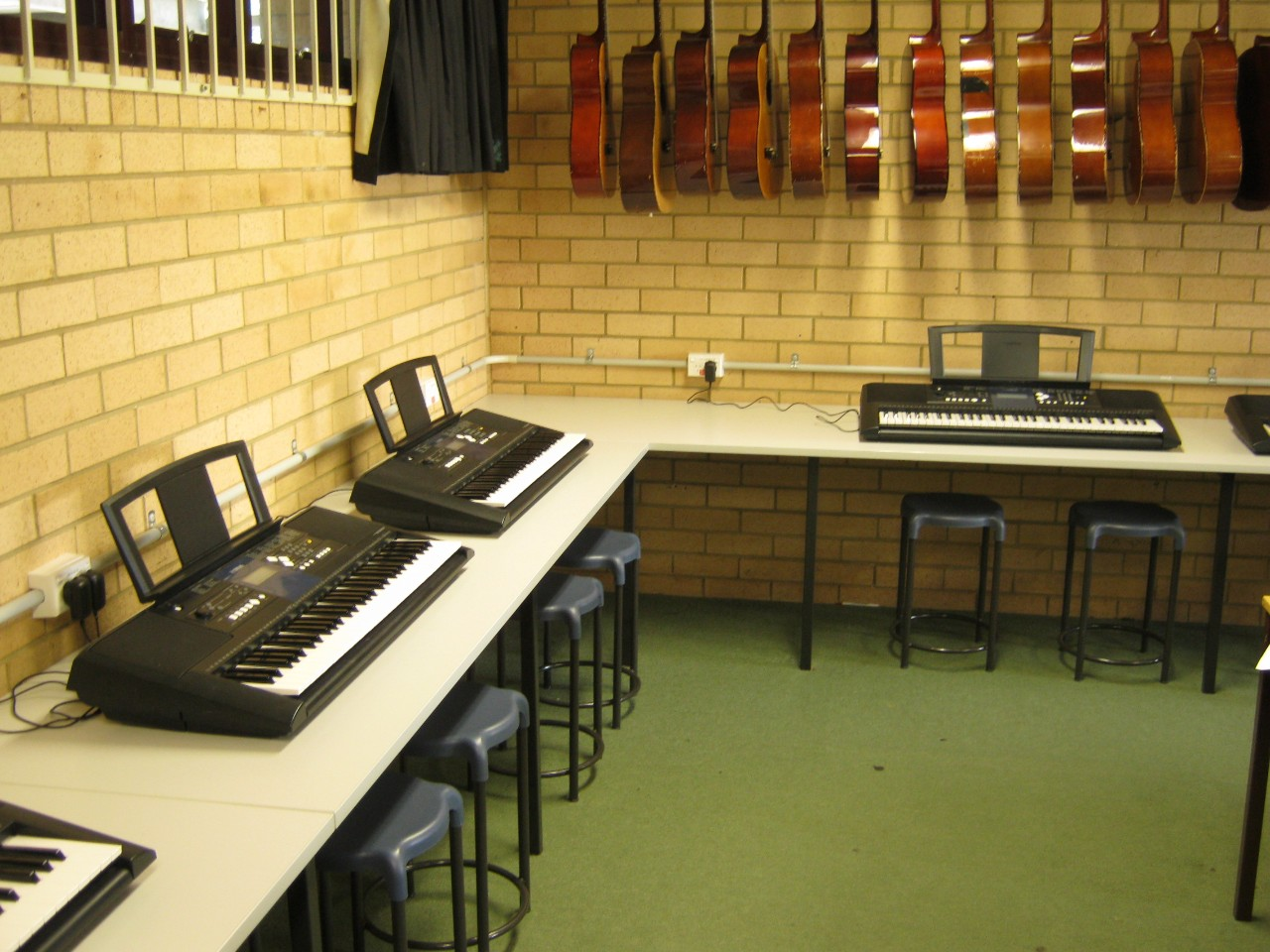 Music room with multiple guitars hanging and keyboard pianos around the outside.